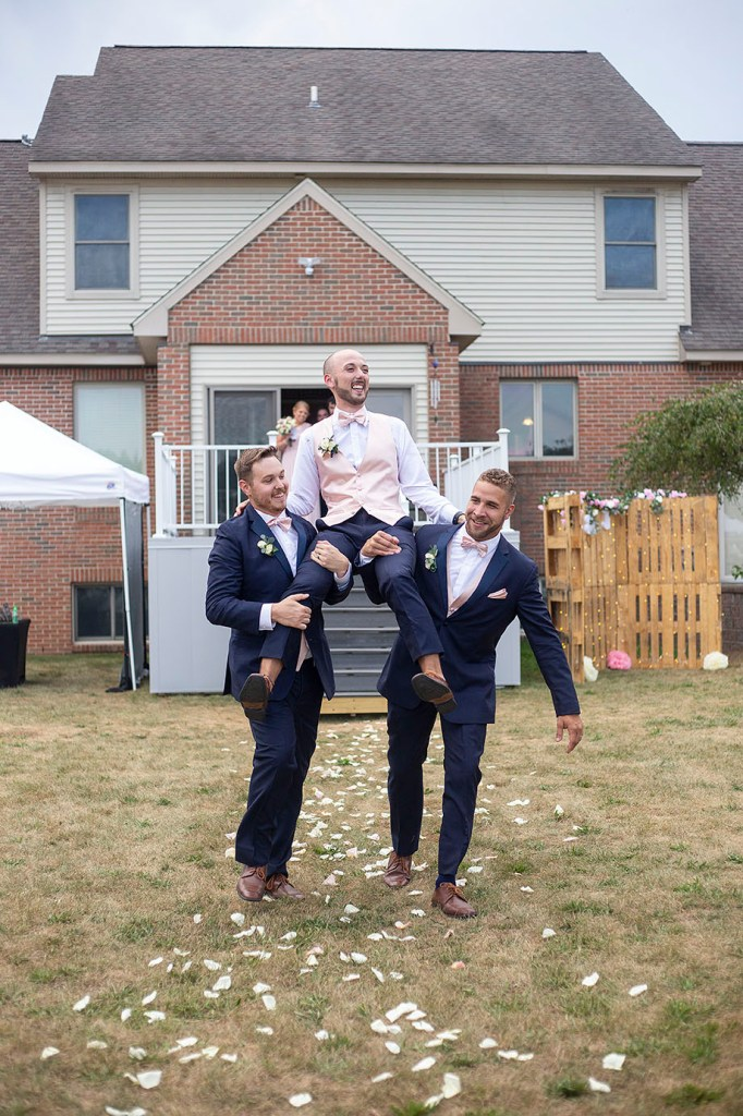 Bridesman getting carried by two groomsmen