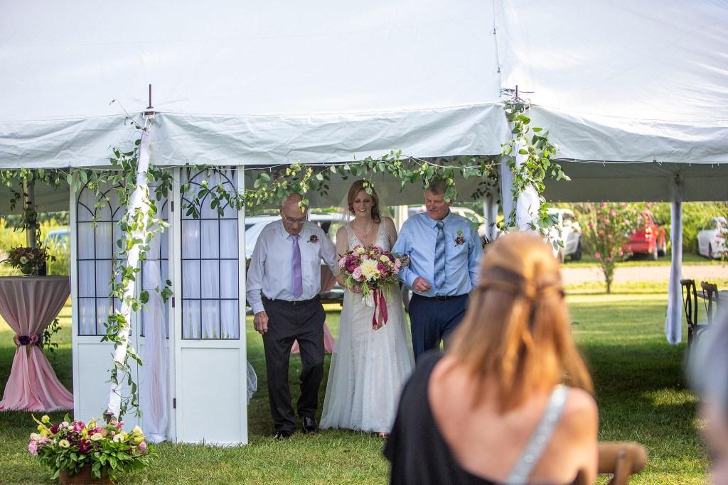 Bride emerging from tent at Belleville wedding