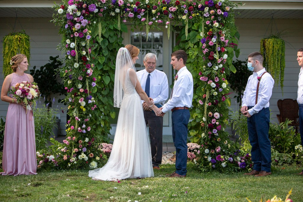 Bride and groom at floral altar