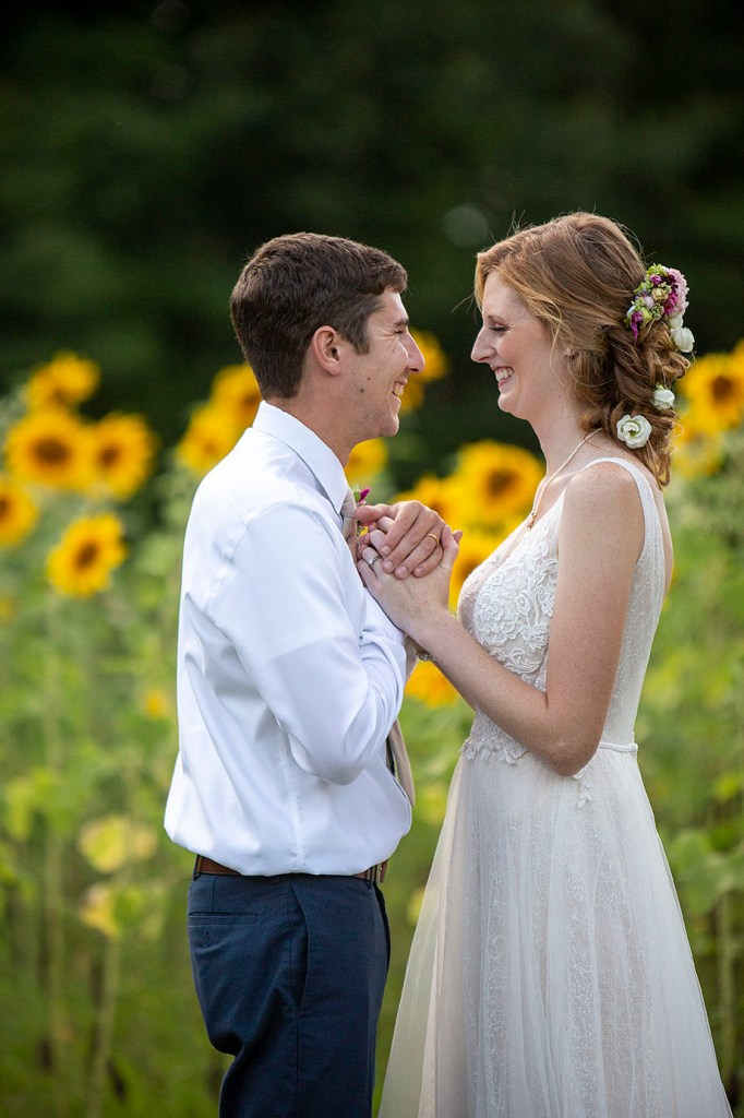 Carmen and Chris look at each other in front of sunflower field