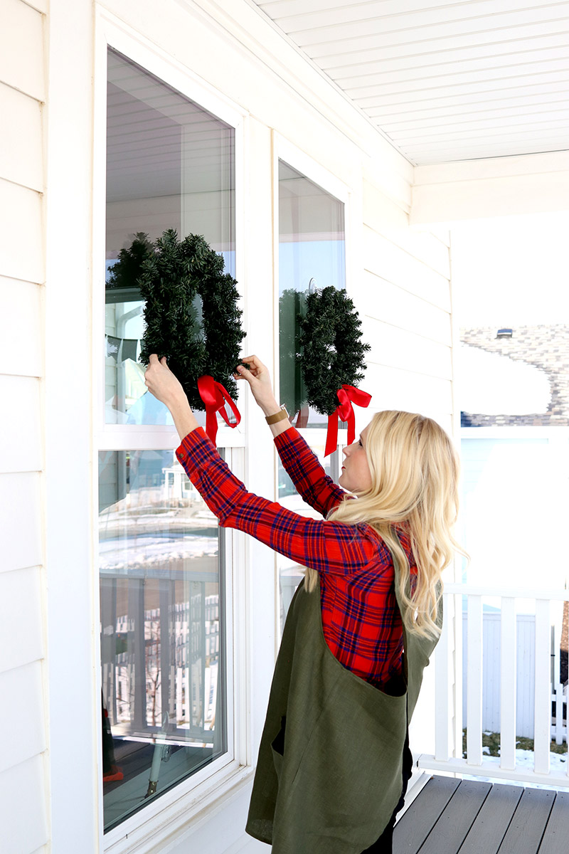 woman holding christmas wreath suction apron ribbon hang wash window home house diy how to