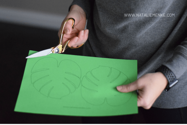 woman's hands using scissors to cut leaf shapes from green paper
