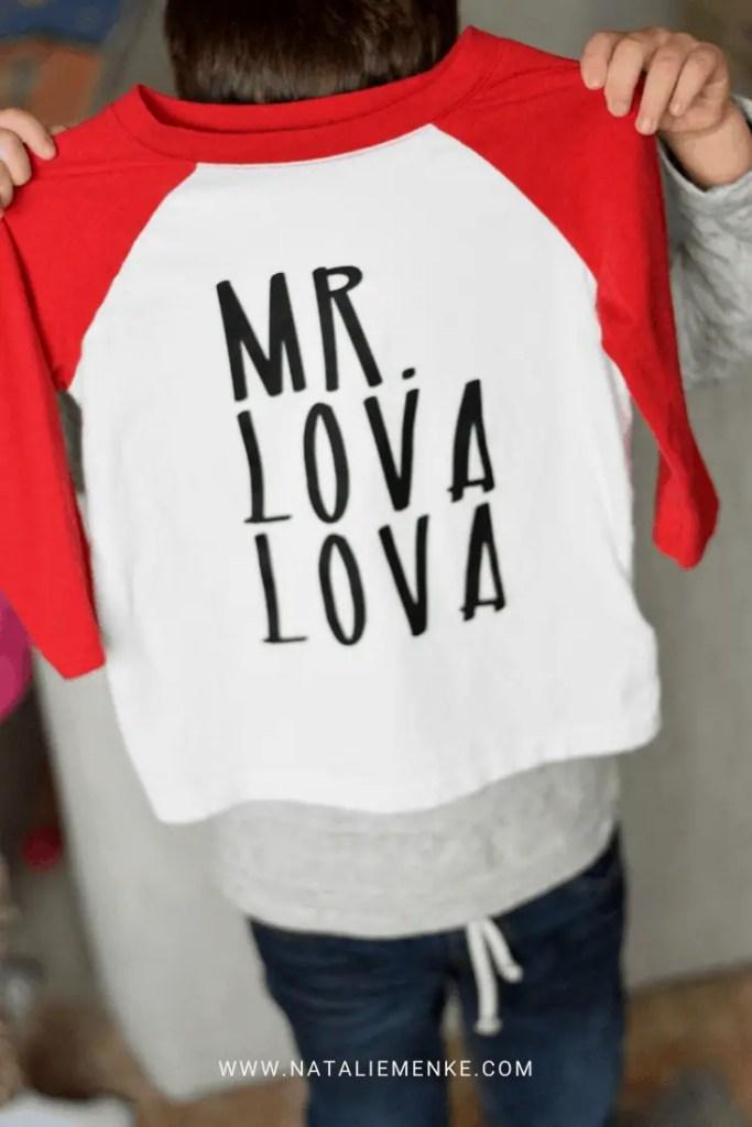 "boy holding a Valentine's Day shirt with ""Mr. Lova Lova"" text"
