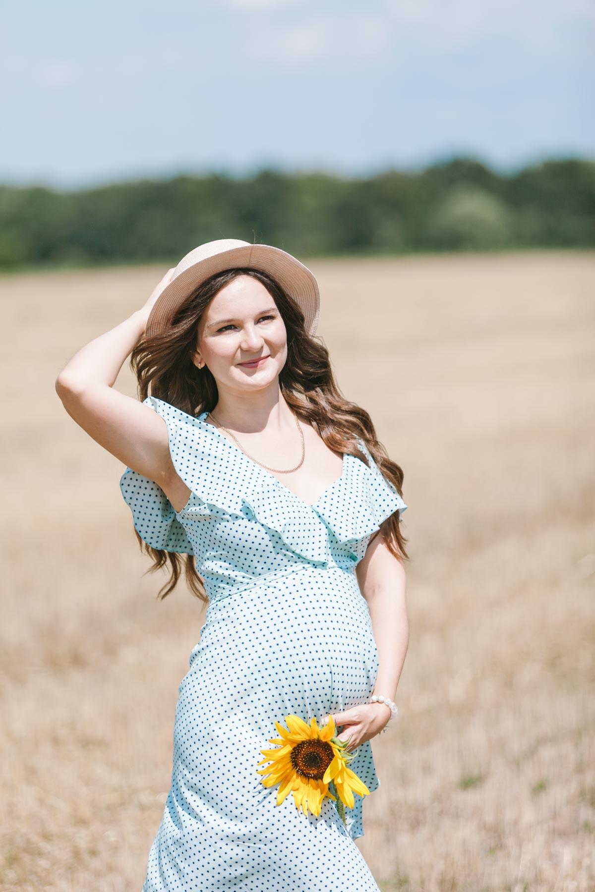 Беременная девушка в голубом платье с подсолнухом в руках