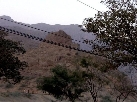 The Stupa behind the power lines lies in ruins.