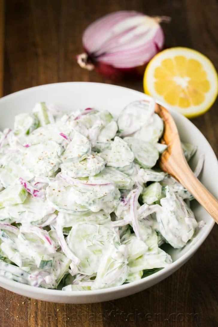 Creamy Cucumber Salad served in a dish with fresh lemon and red onion