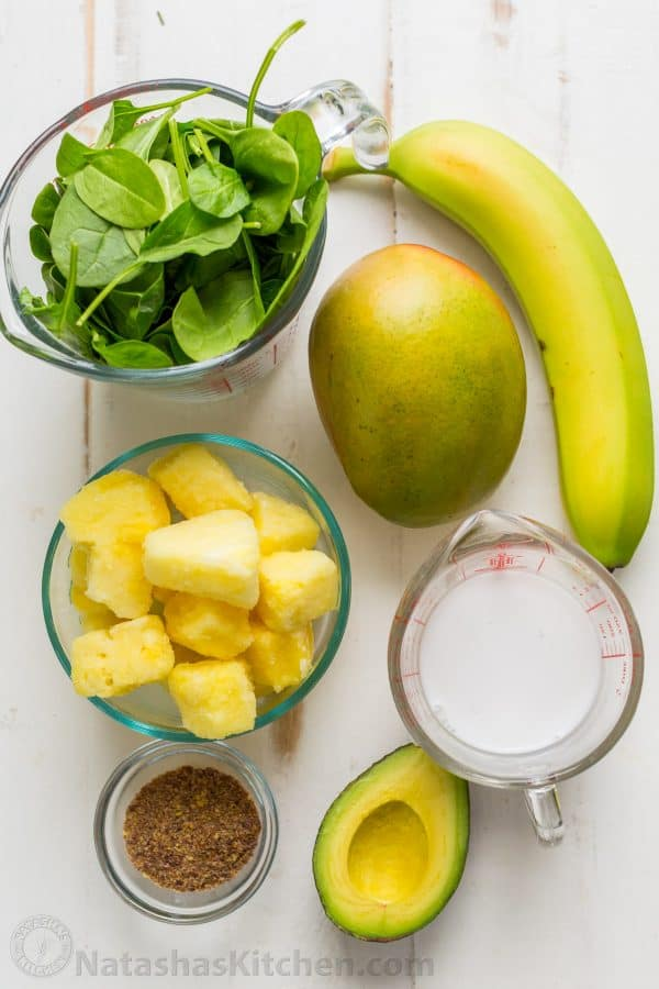 Ingredients for smoothie bowl recipe including mango, avocado, banana, pineapple, spinach, flax seeds and coconut milk