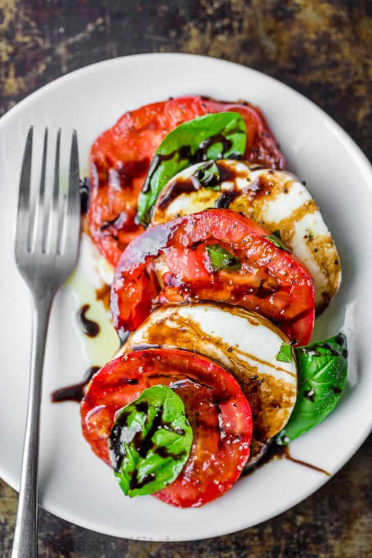 Caprese salad portion on a plate with mozzarella, tomatoes, basil and drizzled with balsamic glaze and extra virgin olive oil