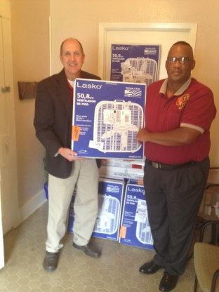 Tripp Dungan, Cleco's principal governmental services representative, and Campti Mayor Roland Smith organize 30 fans Cleco donated to the Campti Seniors Group as part of Cleco's Annual Fan Drive. The fans will be given to seniors to help stay cool and help manage energy bills this summer.
