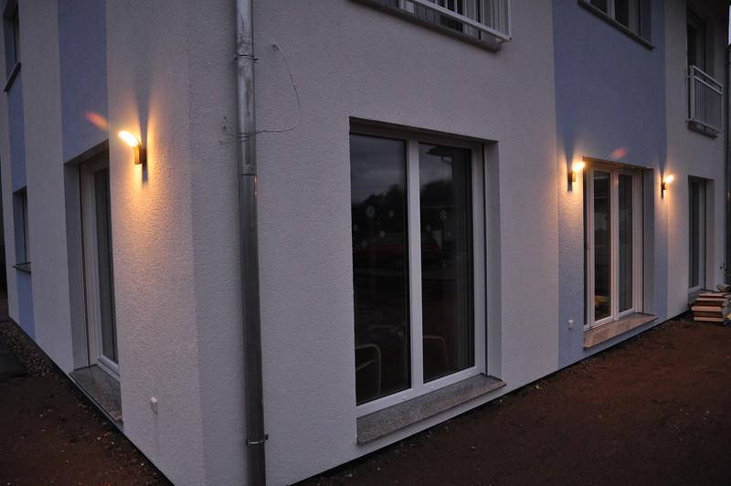 Südwestecke des Hauses mit drei leuchtenden Außenlampen