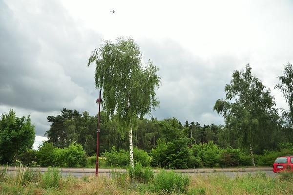 Blick vom Grundstück über die Straße mit Wäldchen und Schönefeld-Flieger