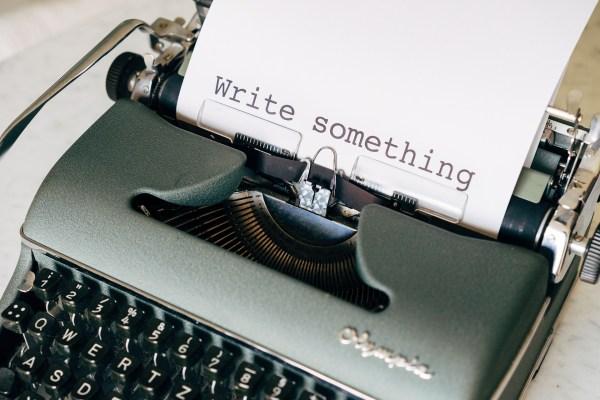 """Machine à écrire avec un papier où il est écrit """"Write something"""""""