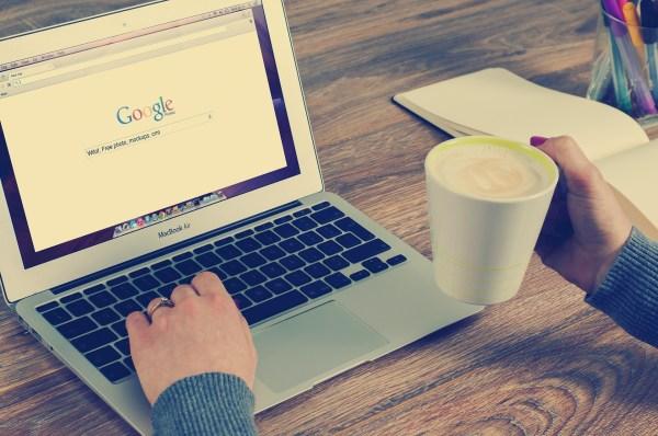 image représentant un ordinateur ouvert sur la page Google et une main tenant une tasse à café