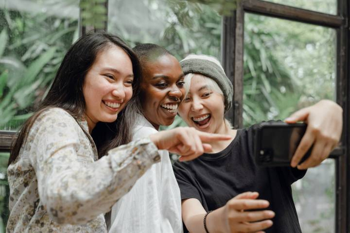 cheerful diverse female friends laughing at just taken selfie