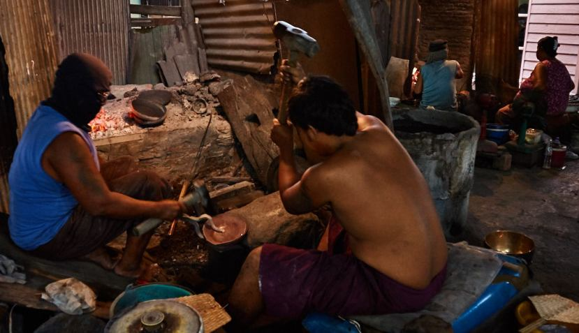Artisans hammering the bronze disc plate into a bowl.