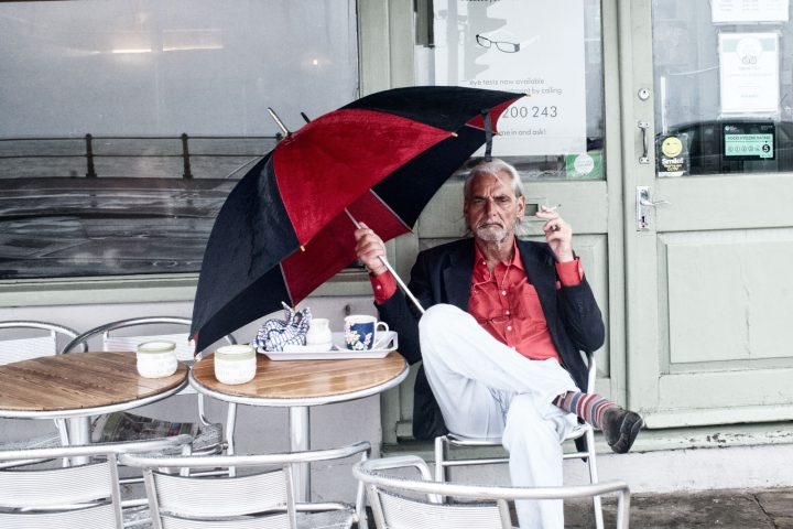 Svelte silver haired chap with red and black outfit and umbrella