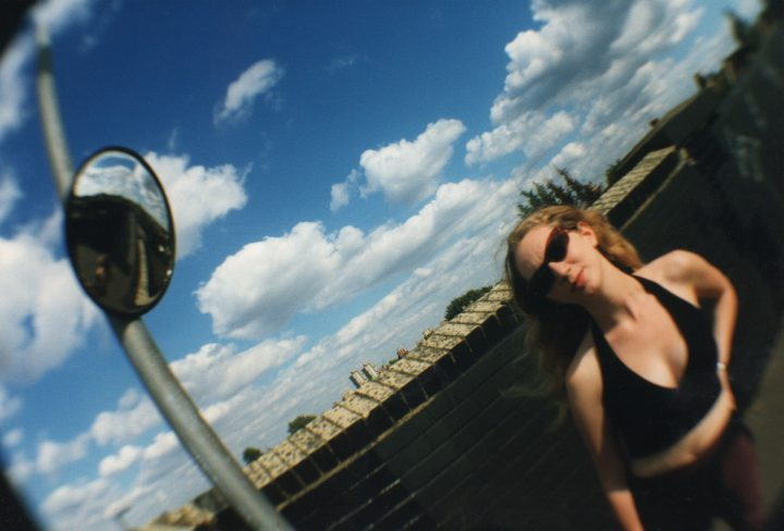 Woman-on-railway-bridge-battersea with little fluffy clouds