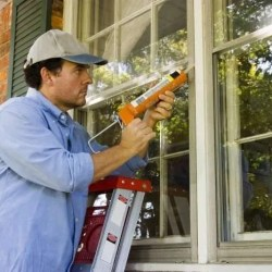 Handyman chaulking a window