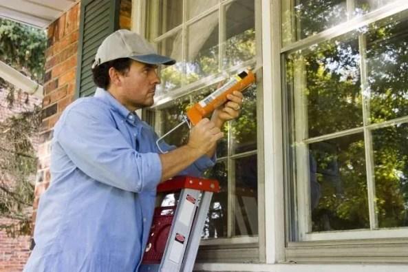 Handyman chaulking a window