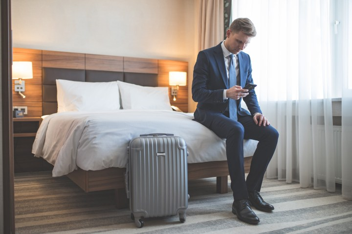 A young man in business formal using his phone while sitting in a hotel room next to a packed suitcase.