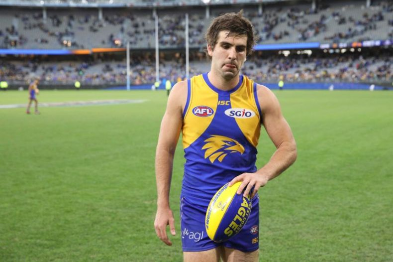 Andrew Gaff holds a football and looks disappointed after the game.