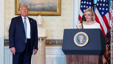 Cleta Mitchell speaks during an event marking the 100th Anniversary of the 19th Amendment ratification with U.S. President Donald Trump, left, in the Blue Room of the White House in Washington, D.C., U.S., on Tuesday, Aug. 18, 2020.