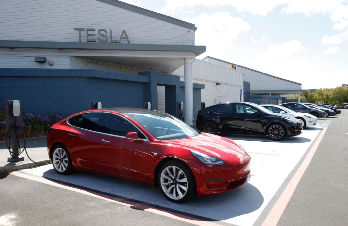 Tesla cars charge at a Tesla Supercharger station in Corte Madera, Calif.