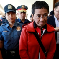 Rappler CEO and Executive Editor Maria Ressa is escorted by police after posting bail in Pasig Regional Trial Court in Pasig City, Philippines, in March 2019.  | REUTERS