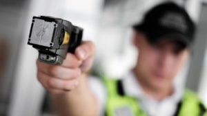 a police officer holding a taser in his hand