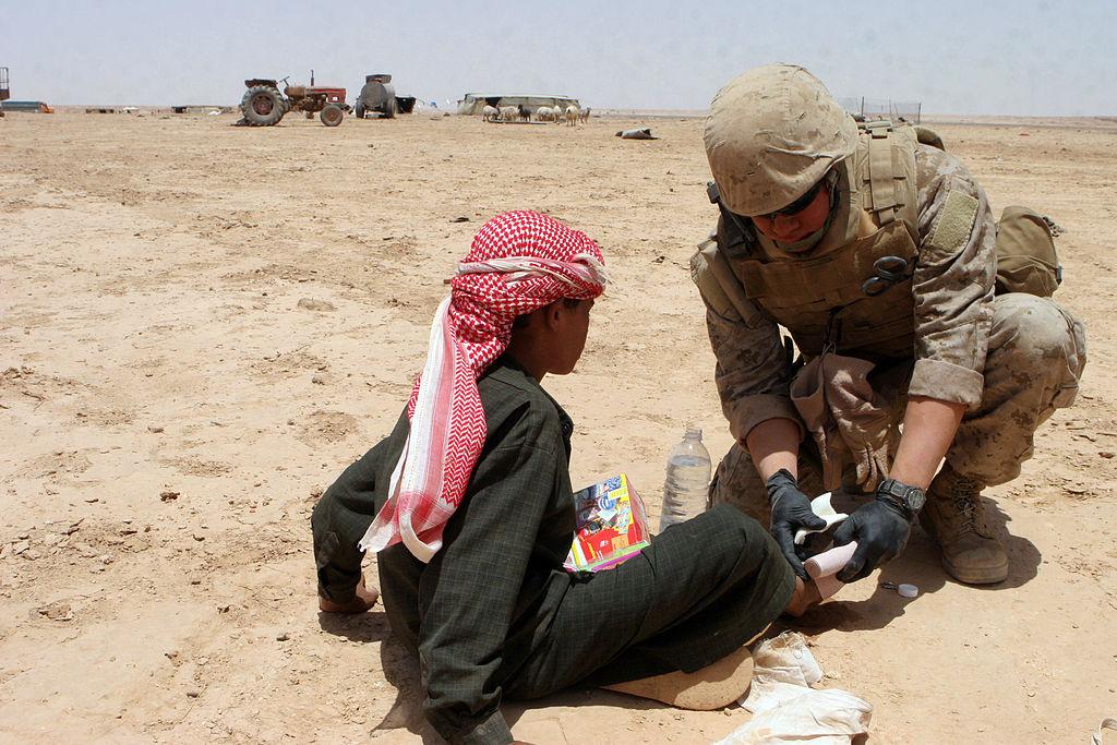 A Corpsman Marine américaine donne des soins médicaux à un enfant irakien dans la province d'Al-Anbar. Wikimedia Commons / US Marine Corps
