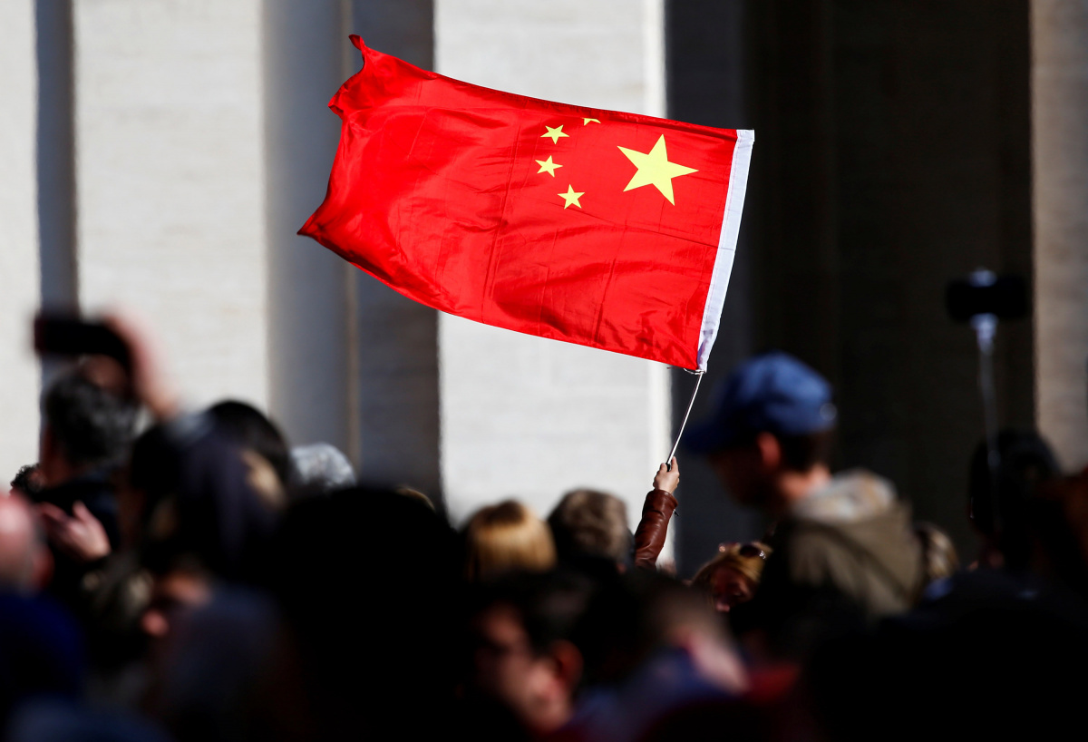A Chinese pilgrim waves a flag, as Pope Francis arrives to lead his Wednesday general audience, in Saint Peter's Square, at the Vatican