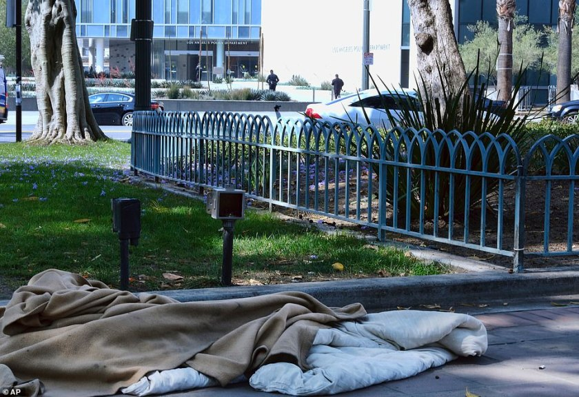 An abandoned sleeping bag and blanket is left in on the grounds of Los Angeles City Hall across the street from Los Angeles Police Department headquarters