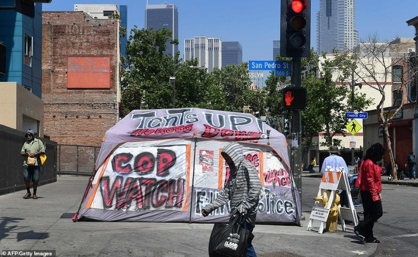 'Sidewalks have disappeared, hidden by tents and the kinds of makeshift shanties you see in Third World places', one local reporter said. Pedestrians walk past a tent for the homeless on a sidewalk in Skid Row, downtown Los Angeles
