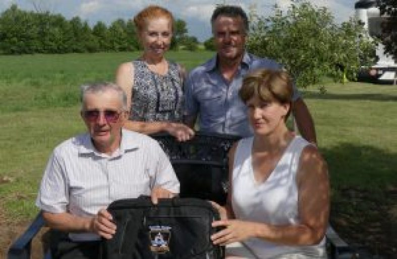 Pictured are the hosts of the Grenville Dundas Stormont Ayrshire Club's annual picnic and 100th annual celebration, Tracy and Ian Porteous of Ayrporte Farm (in back), along with Past President Cynthia Daoust, who presents a new satchel to long-time Treasurer Bruce Garlough. Zandbergen photo, Nation Valley News