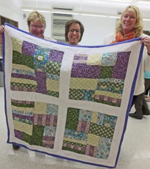 From left, Joan Merkley and a quilt she made and contributed to the  local Quilts for Fort McMurray effort, local organizer  Monique Wilson, and shipping sponsor Darlene McGimpsey. Courtesy photo