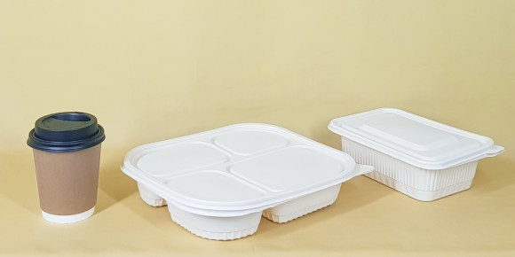 Coffee cup with black lid and two white takeout boxes against a yellow background