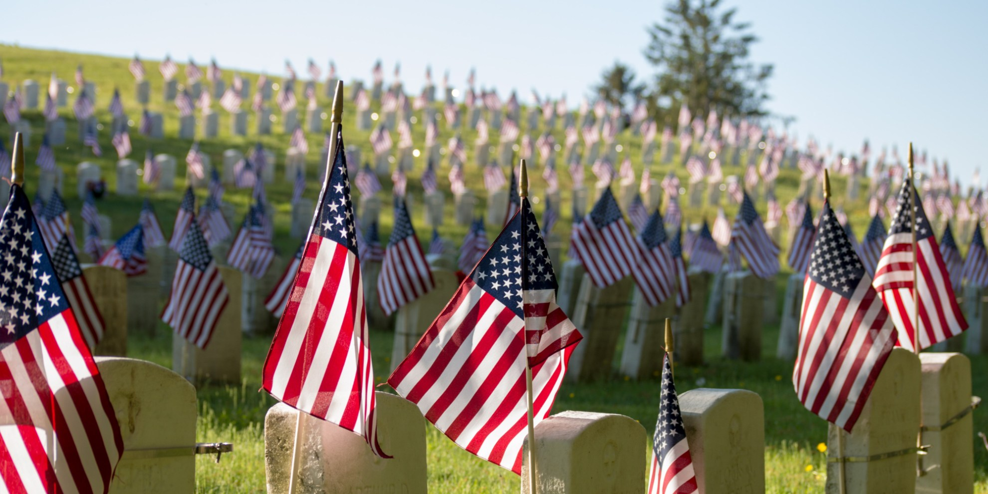 American flags on top of gravestones at cemetery