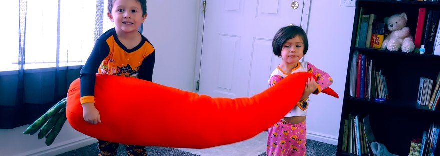 Two kids holding giant carrot