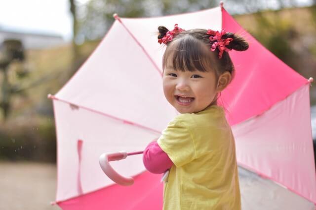 笑顔の女の子が傘を持っている