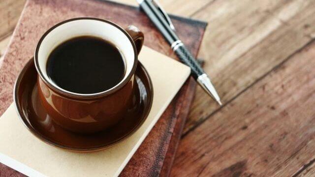 コーヒーカップに入ったコーヒーとペン写真