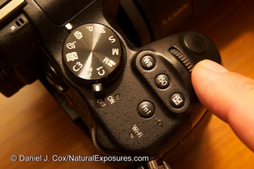 A shot of the top deck of the Lumix GH3 that shows placement of important controls including Shutter Button, Subcommand Dial, WB, ISO, Exposure Compensation, Mode Dial, On/Off switch, Fn button for WiFi.