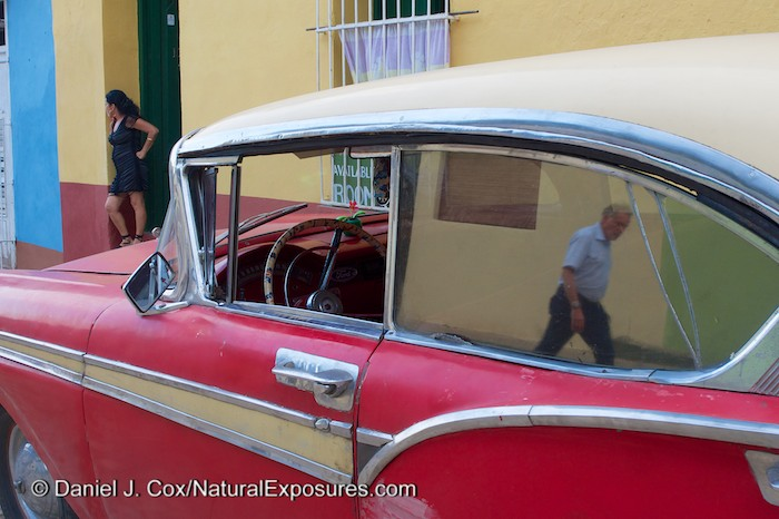 A man passing by an old car is reflected in the window on the streets of Trinidad, Cuba.