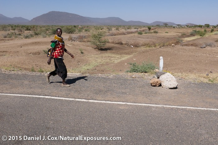 A lady walks the new highway built within the last four years outside of Isiolo, a small town that is scheduled to become a gambling town somewhat like Las Vega. Lumix LX100