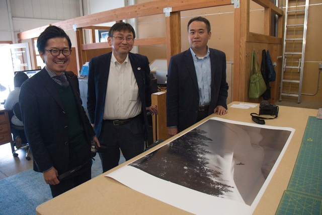 "Panasonic Lumix executives Shinji Watanabe, Henri Nishikawa and Yasuhide Yamada take time out to review one of Daniel's newest print newest print releases ""Raven Spirit"" at the Natural Exposures office in Bozeman, Montana"