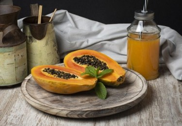 Foods for healthy digestion: Image of cut open papaya and a glass jar of papaya juice.