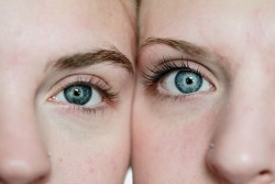 closeup on the the beautiful blue eyes of two women with their faces cheek to cheek