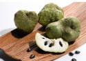 Three whole cherimoya fruits and one sliced on a cutting board