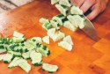 cucumbers being cut into little bite size chunks with a knife