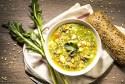 Nutritious soup in a bowl alongside roll of bread