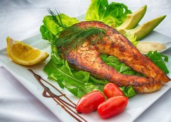 grilled salmon on a plate surrounded by lettuce, avocado, tomatoes, and garnished with a lemon